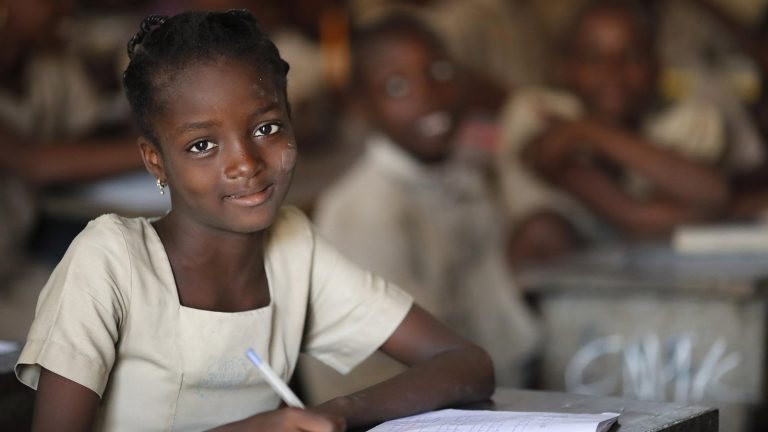 A young African girl sitting at a desk in a classroom. She has a pen in her hand and smiles. Other classmates are sitting around her in the background.