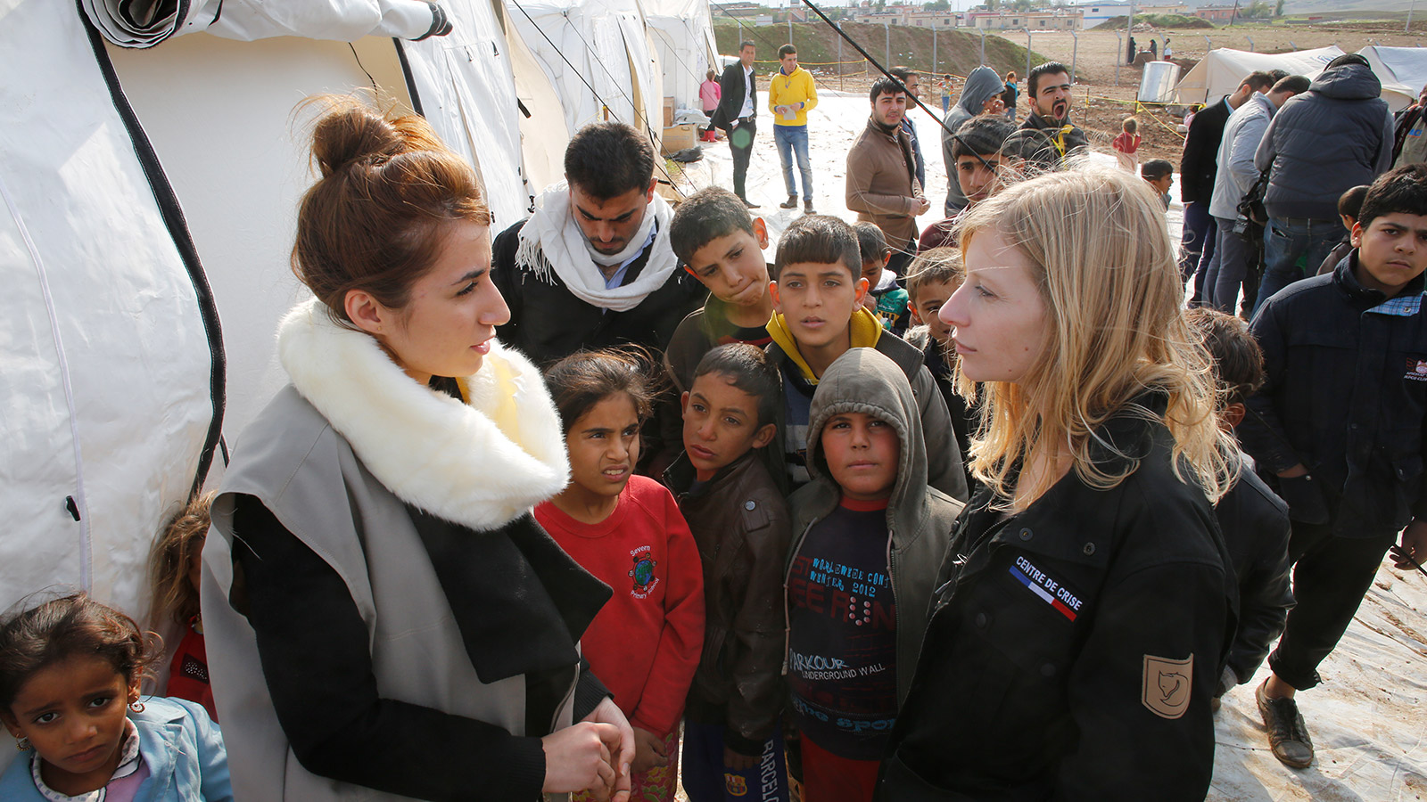 A woman is talking to a French aid worker in front of a row of tents at a refugee camp. Several children and a couple of men are gathering around them.