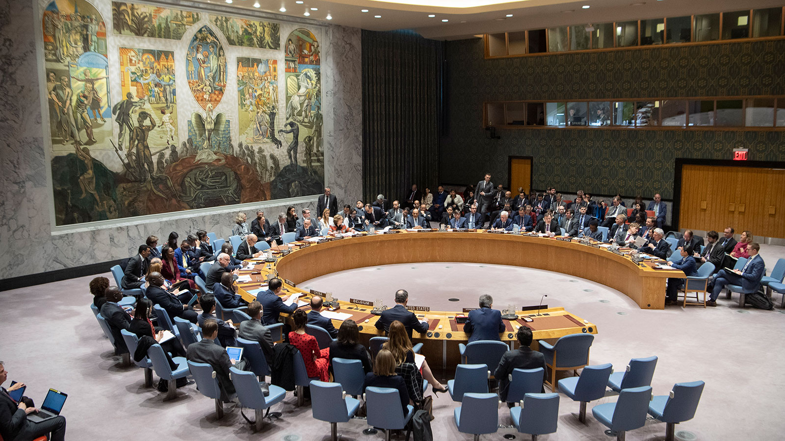 Representatives of UN member states sitting at the horseshoe shaped table of the UN Security Council. On the wall to the left there is a large tapestry displaying ancient sceneries. The glass panes of interpreting booths can be seen at the wall in the background