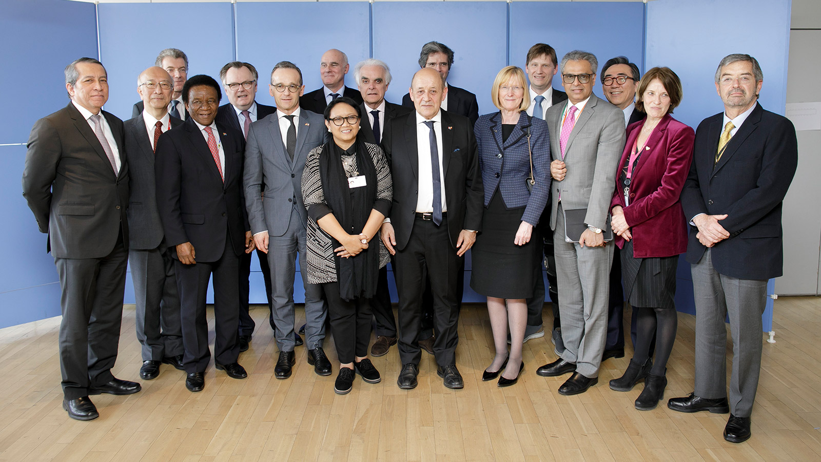 Foreign Minister of Germany, France and Indonesia pose for a group picture with several Ambassadors to the UN against a blue back-drop.
